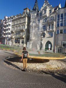 Eine Person steht am Karlsbader Heilbrunnen, Fontäne